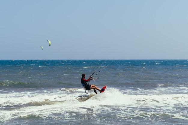 Kitesurfista masculino se mueve en el tablero sobre las olas del mar