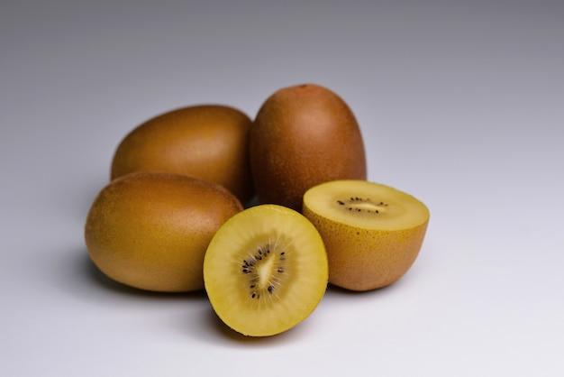 Kiwi actinidia chinensis kiwi dorado entero y cortado sobre fondo gris