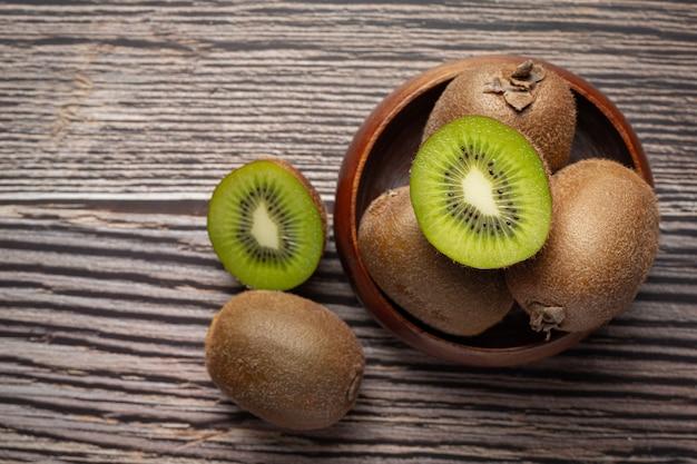 Kiwi fresco, cortado por la mitad, poner en un cuenco de madera