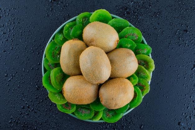 Kiwi fresco en un plato con kiwi seco plano yacía sobre un fondo gris oscuro