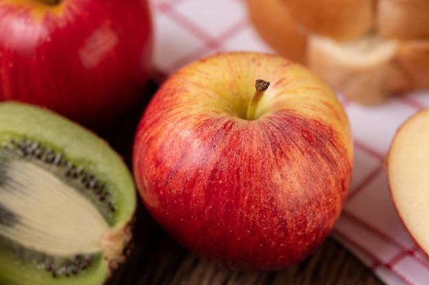 Kiwi, manzanas y pan en la mesa