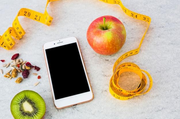 Kiwi a la mitad; frutas secas; manzana; cinta métrica y teléfono inteligente sobre fondo gris con textura