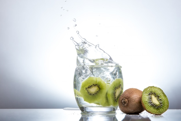 Kiwi en un vaso y salpicaduras de agua. comida sabrosa y saludable. bebidas de temporada. hora de verano. frescura verde