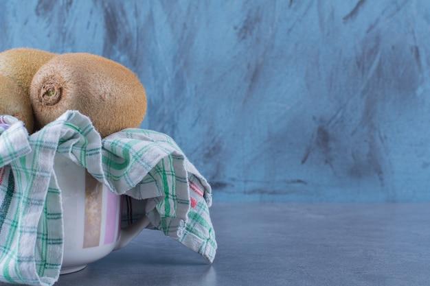 Los kiwis en una toalla en un recipiente sobre una mesa de mármol.
