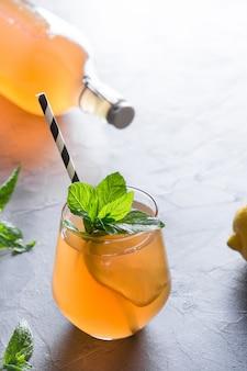 Kombucha casera saludable sabrosa bebida en botella y vaso con guarnición de limón menta. bebida probiótica orgánica