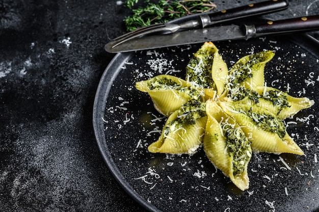 Konkiloni italian jumbo conchas de pasta conchiglioni rellenas de carne de vacuno y espinacas en un plato.