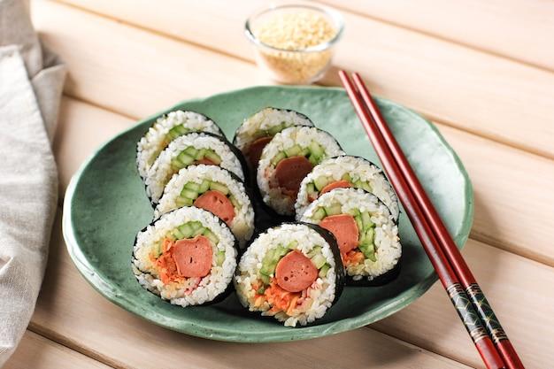 Korean roll gimbap (kimbob o kimbap) hecho de arroz blanco al vapor (bap) y varios otros ingredientes, como kyuri, zanahoria, salchicha, palito de cangrejo o kimchi y envuelto con algas marinas. copia espacio