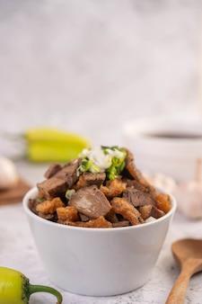 Kuay jab en una taza con albóndigas de cerdo y galleta de cerdo.