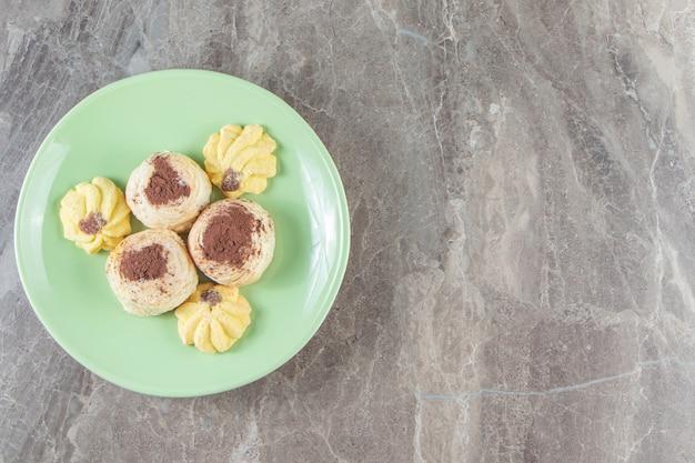 Kue semprits y cacao en polvo sobre galletas de mantequilla en un plato de mármol.