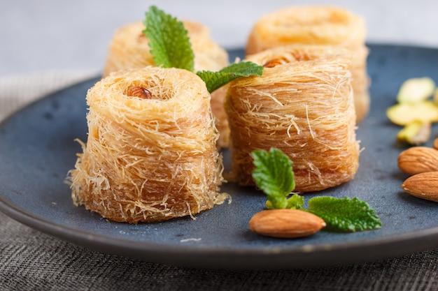 Kunafa, dulces árabes tradicionales en placa de cerámica azul sobre un hormigón gris. de cerca.