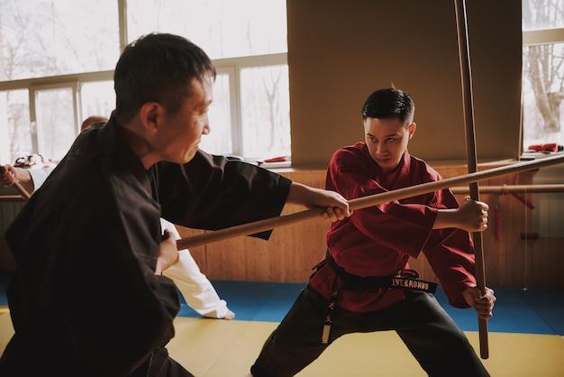 Kung fu luchadores de artes marciales luchando con palos.