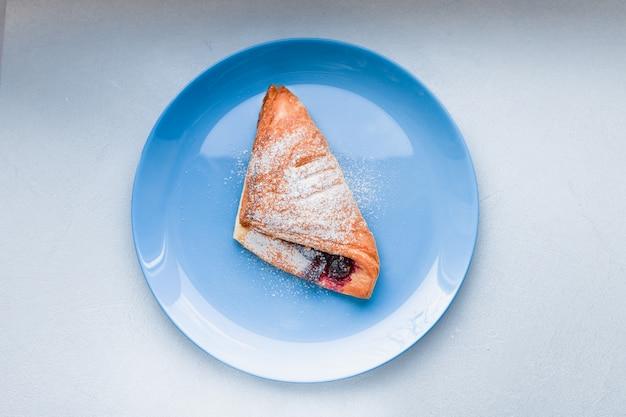 Kurasan en un plato azul. desayuno con curasan y café en una mesa blanca. en un plato azul con bayas repostería casera