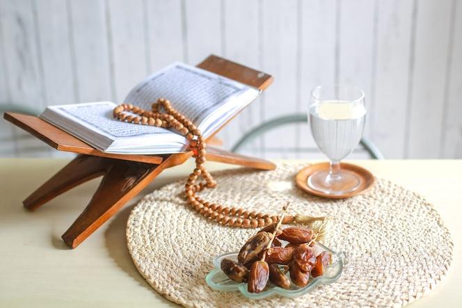 Kurma o dátiles con vaso de agua, sagrado corán y cuentas de oración sobre la mesa