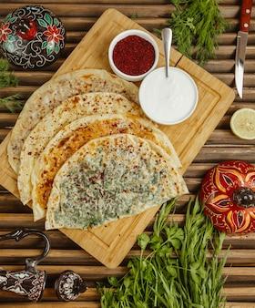 Kutab de comida rápida caucásica tradicional servido con salsas en un plato de madera