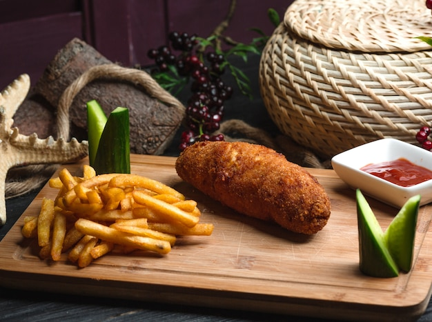 Kyiv cotlete con papas fritas sobre tabla de madera