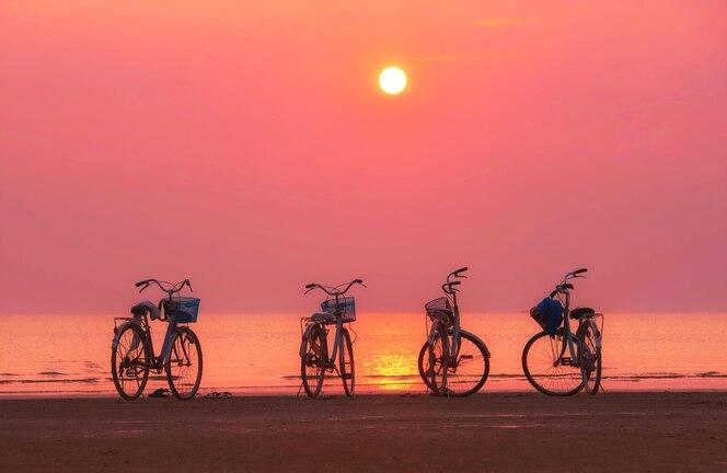 La bicicleta está en la playa y la luz del atardecer en el cielo