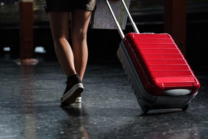 La caminata de la mujer en la estación de tren va de color rojo del bolso de la fricción del viaje, concepto del viaje