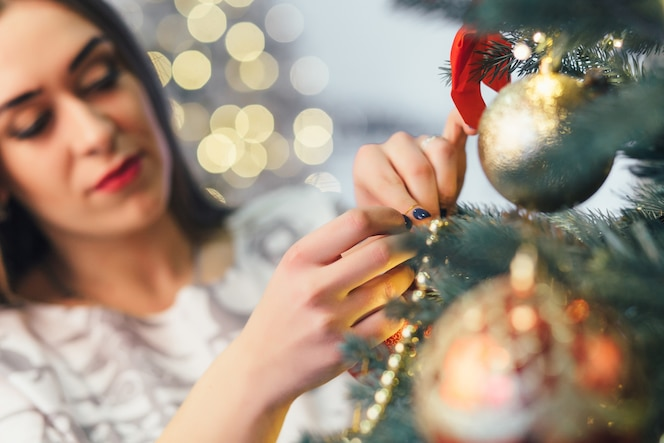 La chica elegante decorando un árbol de navidad
