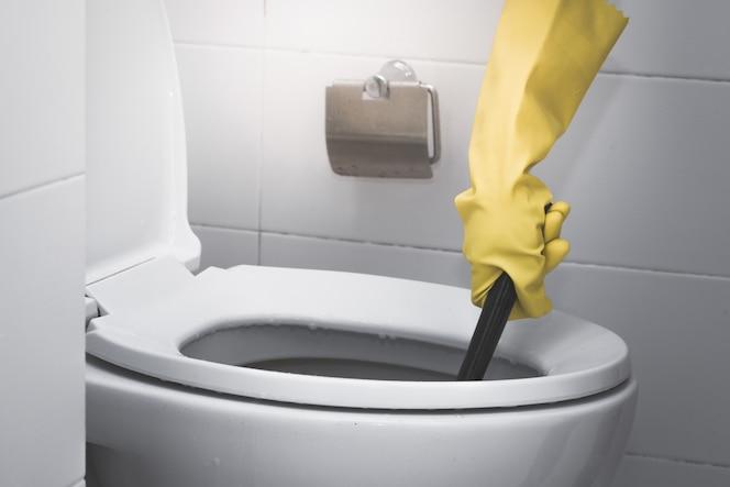 La criada que lleva el guante de goma amarillo y que usa la limpieza del cepillo en el retrete