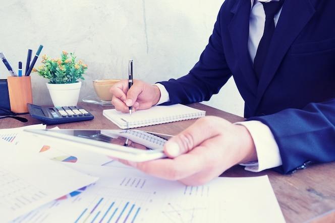 La escritura de la pluma del hombre de negocios analiza las ganancias de la compañía