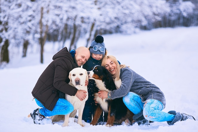 La madre, el padre, el hijo y los perros sentados en la nieve