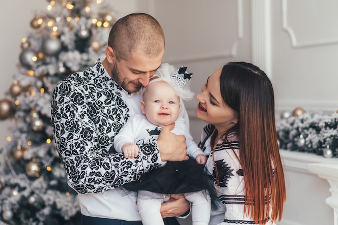 La madre y el padre abrazando a su hija y de pie cerca del árbol de navidad