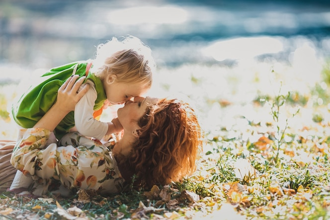 La madre y la hija se encuentran en la hierba