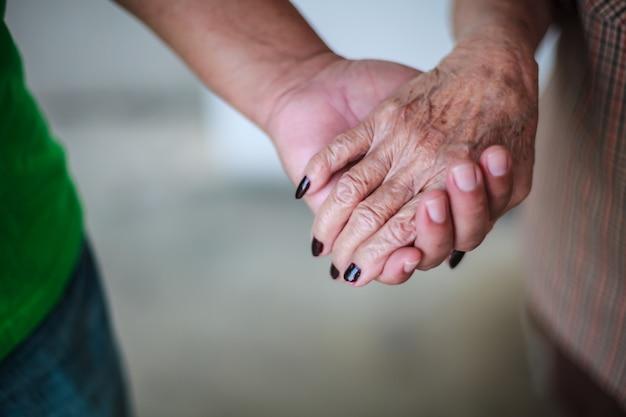 La mano arrugada de la mujer mayor que se sostiene a la mano del hombre joven. relación familiar.