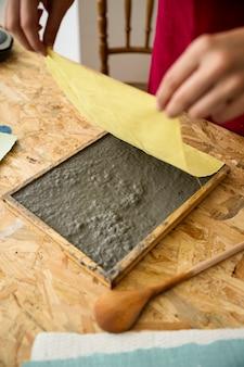 La mano de la hembra que coloca el paño amarillo sobre la pulpa de papel sobre el escritorio de madera
