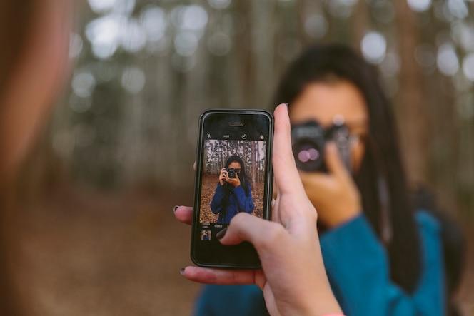 La mano de la mujer que toma la imagen de su amigo que sostiene la cámara