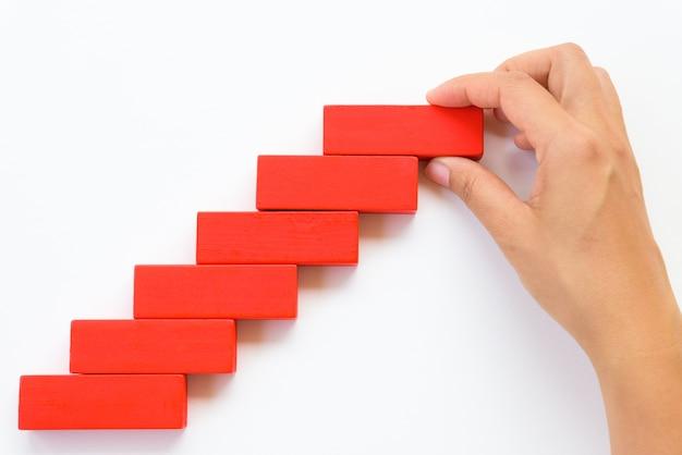 La mano de las mujeres puso el bloque de madera rojo en bloques de madera amarillos en la forma de una escalera.