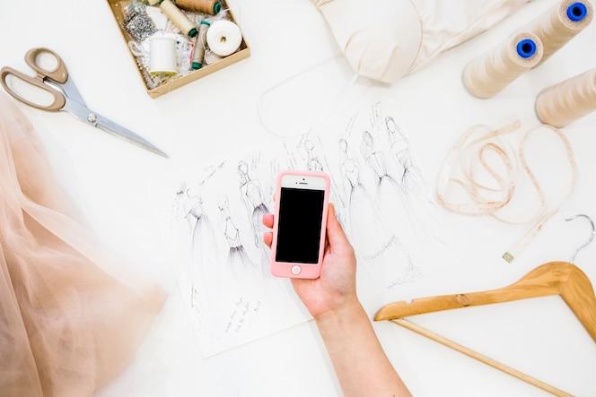 La mano del diseñador de sexo femenino que sostiene el teléfono móvil sobre bosquejo de la manera