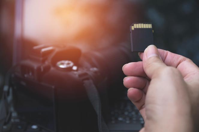 La mano del fotógrafo que sostiene la tarjeta de memoria para preparar su cámara antes de la fotografía.