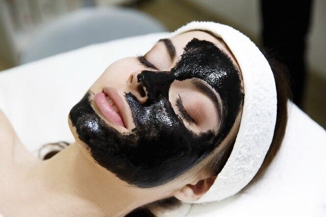 La muchacha con la máscara negra miente en la tabla en salón del balneario