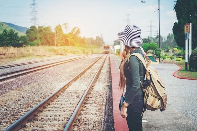 La mujer del viajero que camina y espera entrenan en la plataforma ferroviaria
