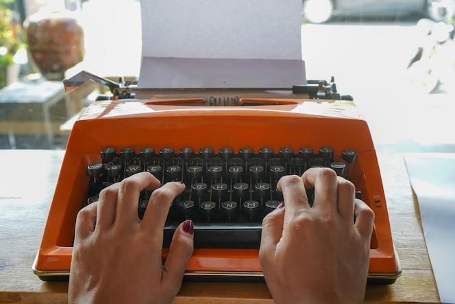 La mujer está escribiendo en una vieja máquina de escribir.