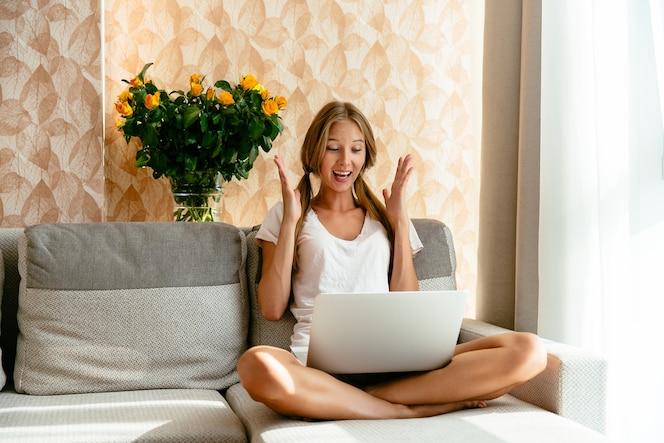 La mujer hermosa vio la sorpresa alegre en la computadora portátil que se sentaba en el sofá en casa