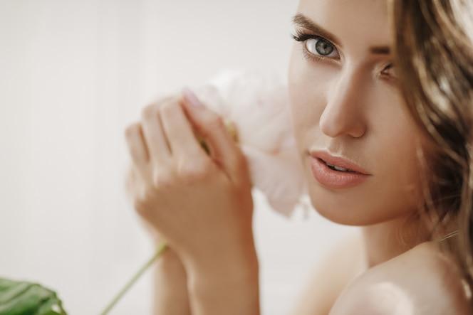 La mujer joven adorable sostiene la flor blanca antes de su cara
