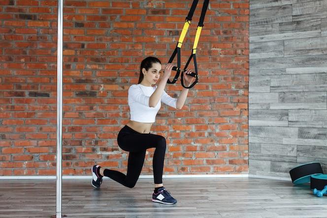 La mujer joven apta hace estiramientos, empuja hacia arriba y levanta los anillos de gimnasia en el gimnasio