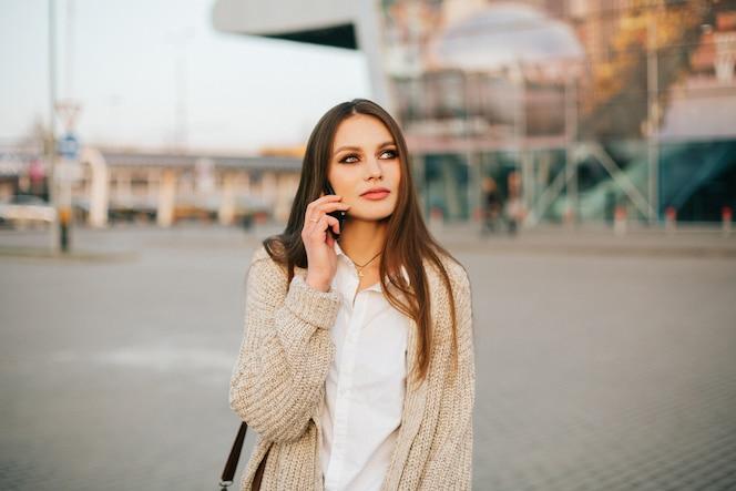 La mujer joven con el pelo largo habla en el teléfono que camina afuera en la tarde