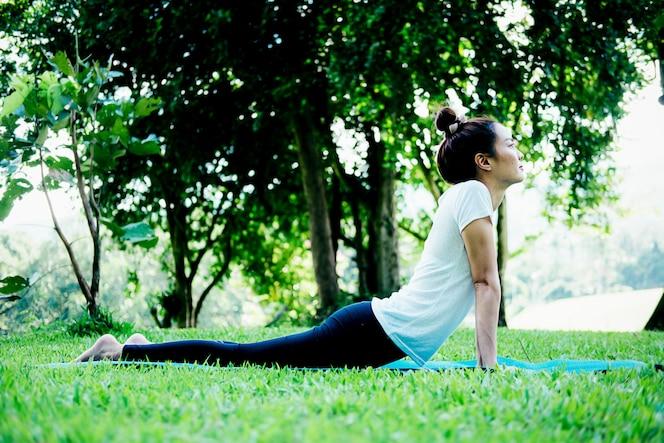 La mujer joven medita mientras que practica yoga en parque.
