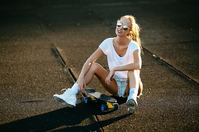 La mujer joven se sienta en una patineta con sus gafas de sol encendido durante la puesta del sol.