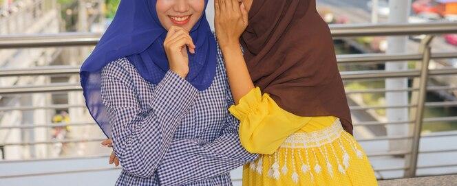 La mujer musulmana está susurrando a otra