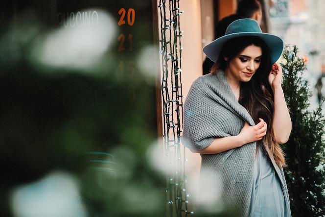 La mujer sonriente en sombrero y suéter se coloca en vestido ligero en una calle del invierno