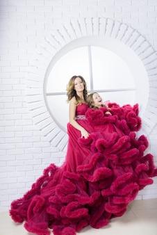 La mujer y su pequeña hija en vestidos rosados se sientan en el alféizar