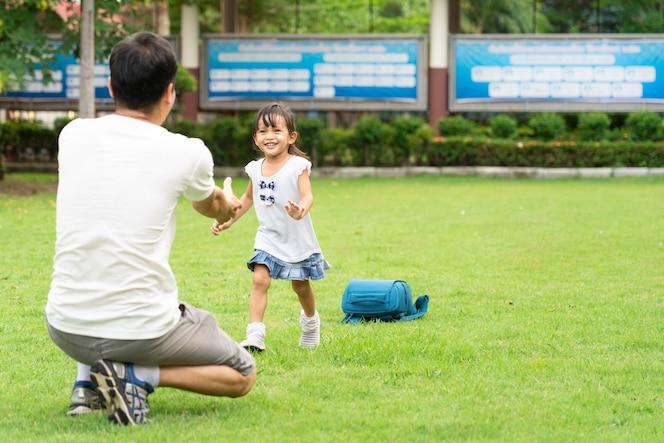 La niña asiática corre hacia su padre después del horario escolar
