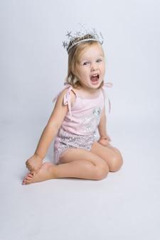 La niña divertida vestida como una princesa se sienta en el estudio