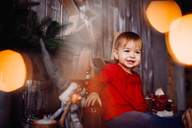 La niña sonriente se sienta en el estante entre las decoraciones hermosas de la navidad