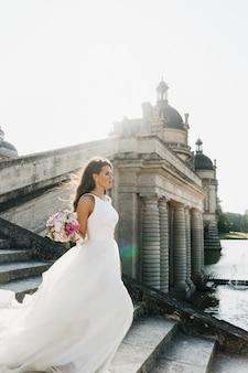 La novia baja las escaleras antes de las columnas sobre el río en paris