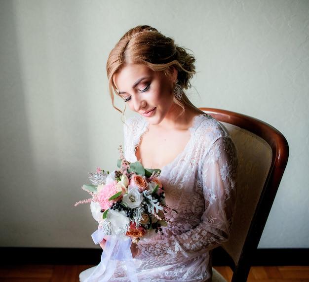 La novia rubia encantadora en traje blanco atractivo se sienta con el ramo de la boda en la silla